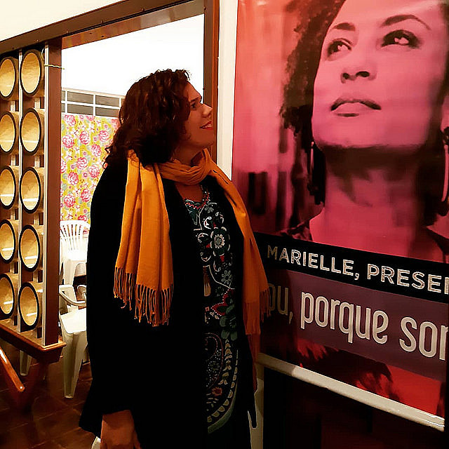 Candidate Fernanda Camargo looks at a poster of Rio de Janeiro councilwoman and human rights activist Marielle Franco