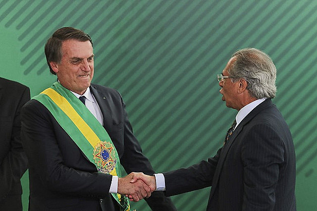 Brazilian president Jair Bolsonaro (right) shakes hands with his economy minister and author of pension reform draft proposal, Paulo Guedes