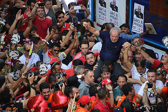 Luis Inicio Lula da Silva is greeted by supporters on Saturday before turning himself in to federal police