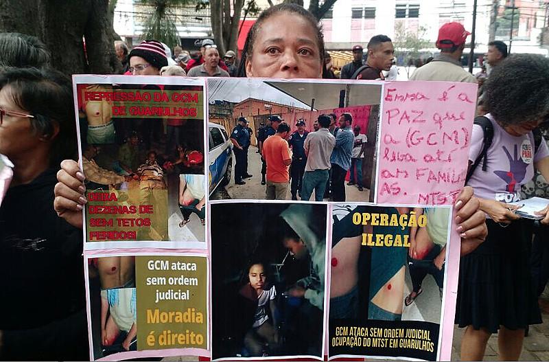 Militante mostra cartaz com fotos de feridos na desocupação de sábado (10)
