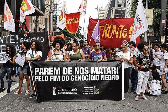"""Los manifestantes sostienen una pancarta que dice """"¡Dejen de matarnos! Por el fin del genocidio negro"""" durante una marcha en São Paulo"""