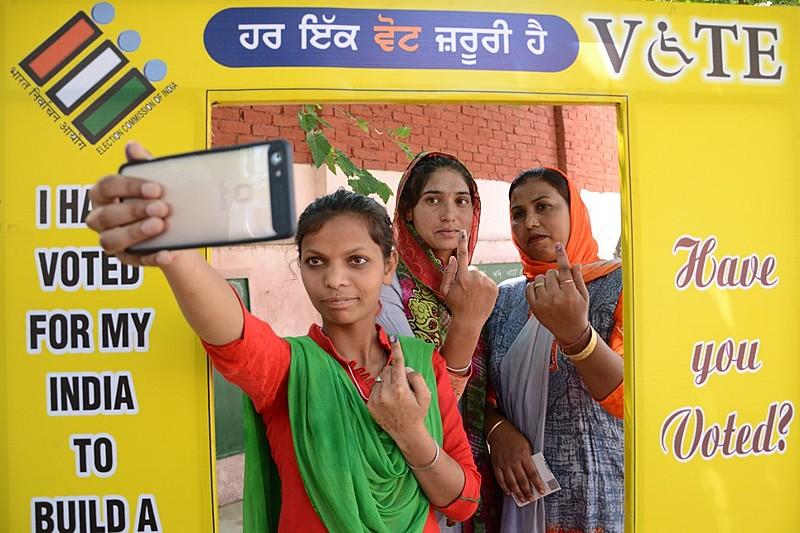 Eleitoras posam para foto mostrando indicador marcado com tinta na periferia de Amritsar na última fase das eleições indianas