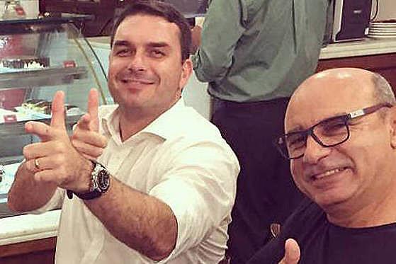 """Flávio Bolsonaro e Fabricio Queiroz fazem o gesto da """"arminha"""", uma das marcas da campanha presidencial do PSL em 2018"""