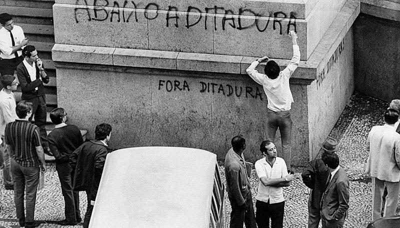 Jovem picha a fachada do Teatro Municipal do Rio durante a passeata de 1968