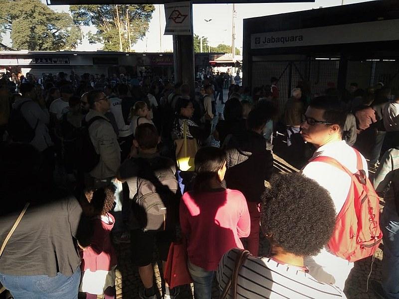 Trabalhadoras e trabalhadores aguardam em frente aos portões por informações sobre o funcionamento do transporte