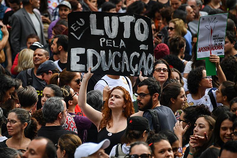 Mulher segura placa de protesto durante o Tsunami pela Educação, dia 15 de maio