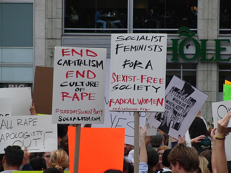 """""""Fim ao capitalismo e à cultura do estupro"""" e """"Feministas socialistas por uma sociedade sem sexismo"""", dizem os cartazes"""