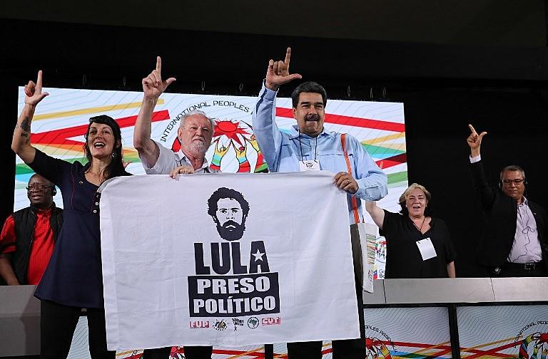 """Maduro levanta uma bandeira com as inscrições """"Lula Preso Político"""" junto ao dirigente do MST, João Pedro Stedile, durante ato na AIP"""