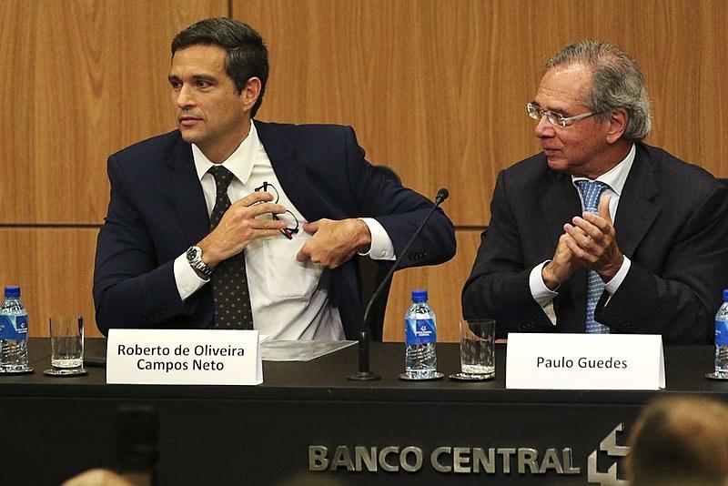 Paulo Guedes (direita) e o atual presidente do BC, Roberto Campos Neto, que passa a indicar conselheiros da nova UIF, antigo Coaf