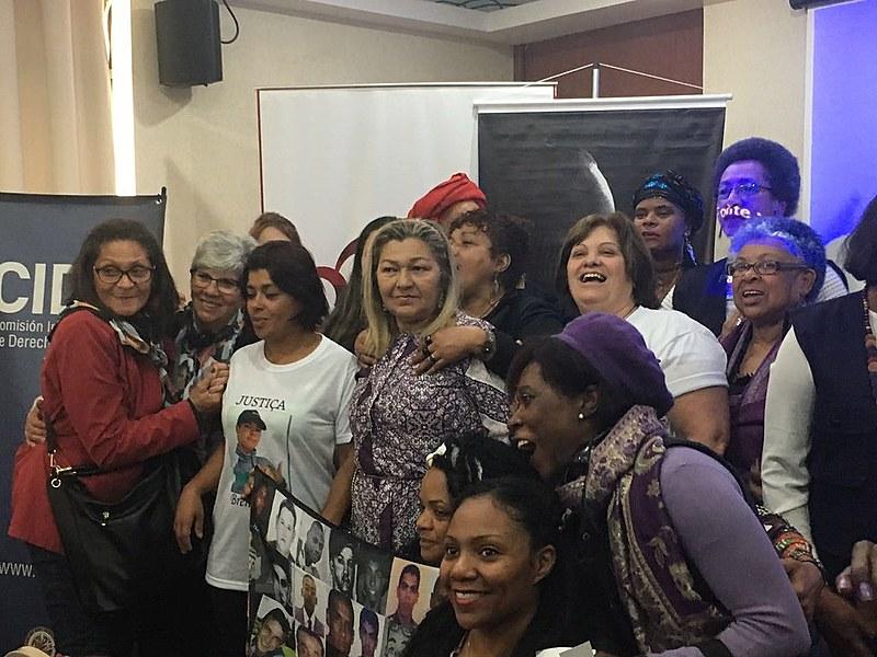 Mães de Maio, Mães Mogianas e outras militantes contra a violência contra mulheres negras tiram foto com relatora de Direitos de Afrodescendentes e Mulheres da OEA, Margarette Macaulay