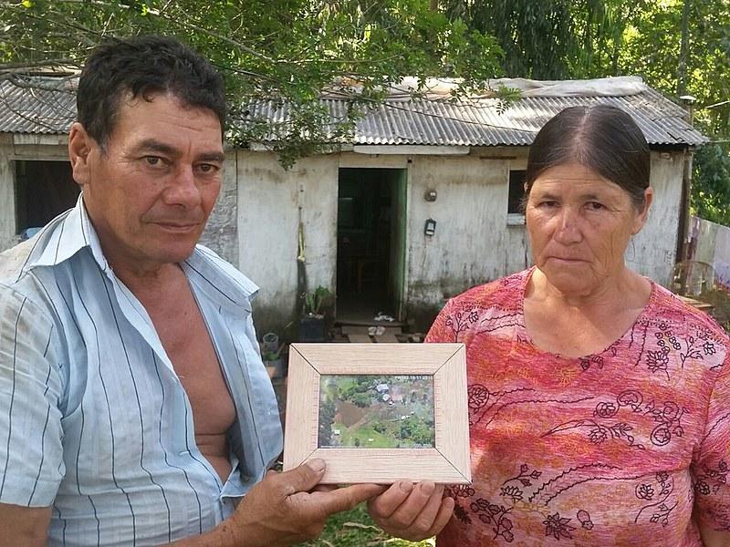 Agricultores Nelson e Eva exibem fotografia do terreno onde viveram por 23 anos. Ao fundo, o casebre para onde se mudaram na sexta-feira