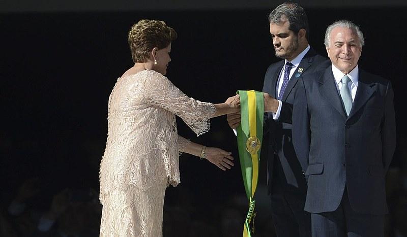 Dilma recebe a faixa presidencial na cerimônia de posse de 1º de janeiro de 2015; à frente, o então vice Michel Temer